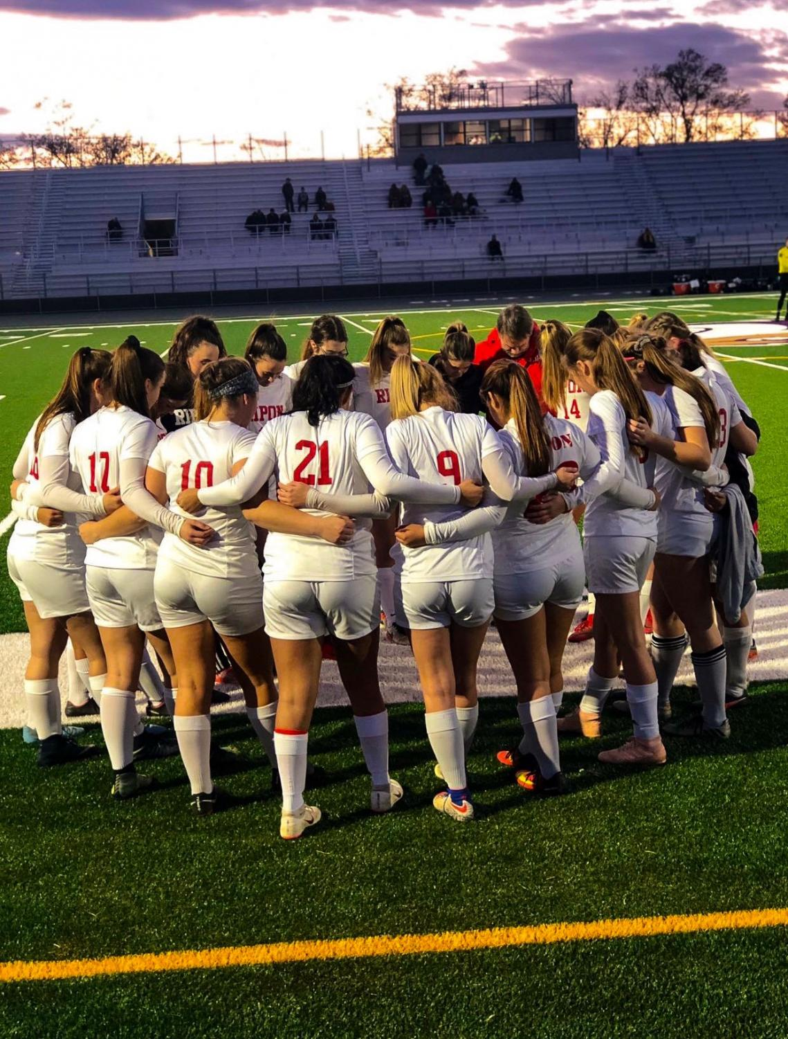 Photo of the team praying before they take the field, to win a sections title. Photo taken by @maddymeyer0506 on Twitter.